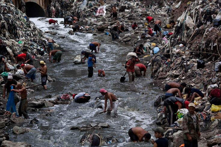 "People search for scrap metal in contaminated water at the bottom of one of the biggest trash dumps in the city, known as ""The Mine,"" in Guatemala City."