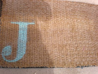 DIY - Use spray paint and a stencil to make a monogram outdoor mat.