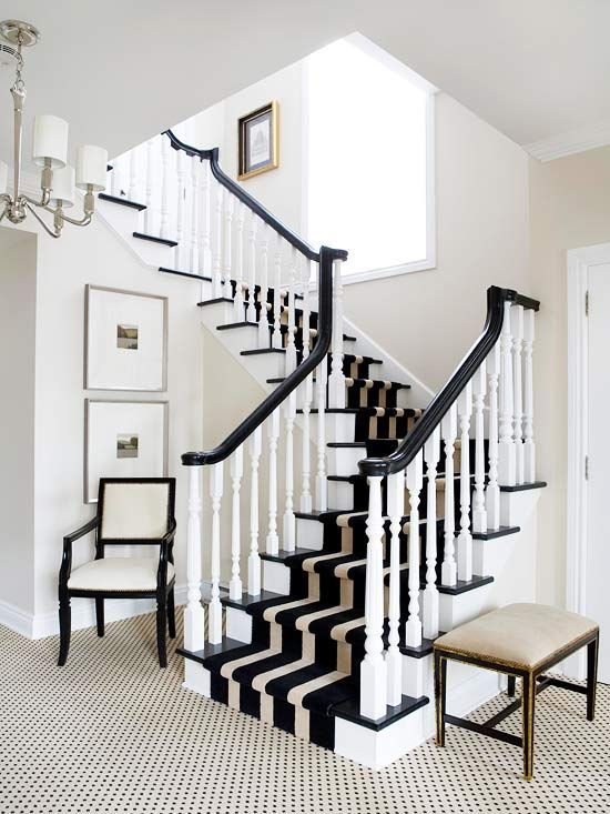 Captivate a visitor's attention and appreciation by furnishing your foyer with high-style furnishings that share a two-note color scheme. Here, a carpet that sports small black motifs running on the diagonal leads the eye to a strikingly striped runner stepping up the stairs. A pretty upholstered chair and bench contribute sculptural forms that further the black-and-off-white scheme./