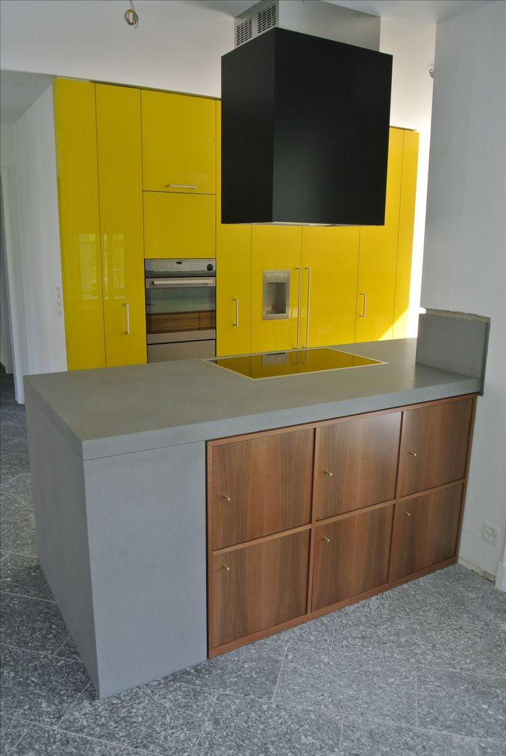 Cucina su misura open space con parete attrezzata in legno laccato giallo e penisola in pietra e noce nazionale; cappa di aspirazione rivestita con pannelli laccati laccati nero semi-opaco.