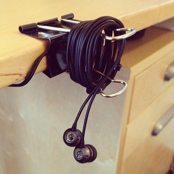 DIY Office Hack use binder clips to keep headphones and phone cords  organised.