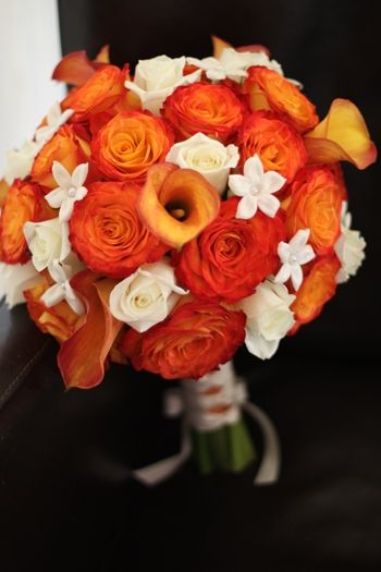 Warm and sunny orange rose, white rose, orange calla lily, and white stephanotis bouquet.