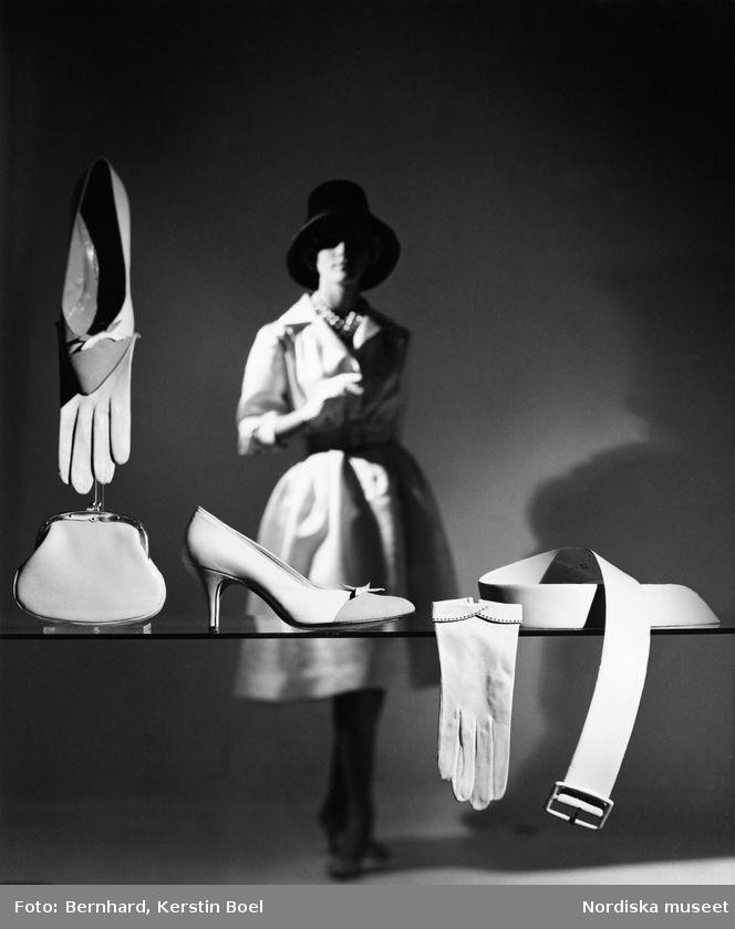 Modell klädd i vit kappa, handskar och hatt. I förgrunden, ljusa pumps, portmonnä, handskar och skärp på en glasskiva. Foto: Kerstin Bernhard, 1950/1955