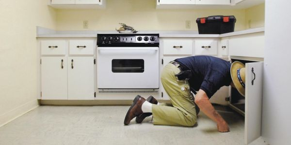 """""""You have to be a detective,"""" says Wayne Walker, senior pest-control technician for the U. of Florida, as he inspects a student's kitchen cupboards."""