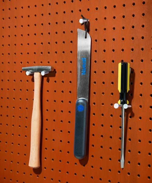 shop tools hung up on peg board with golf tees in a workshop