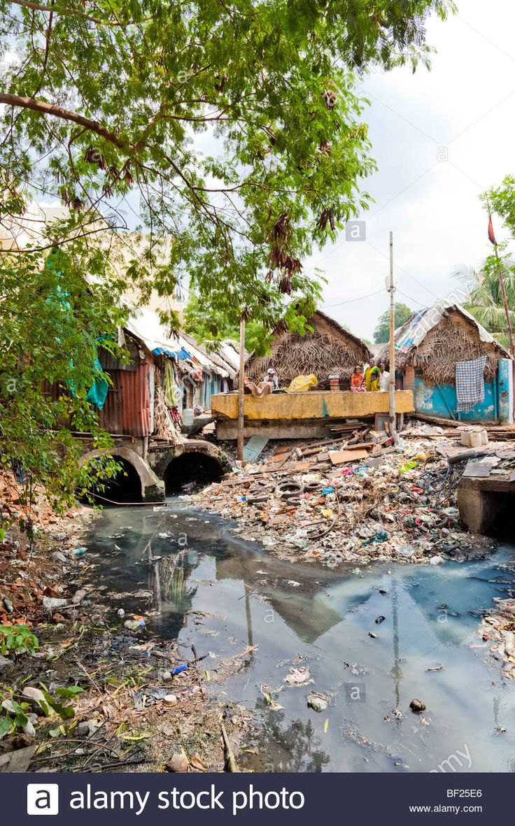 Shanty town next to a heavily polluted river and trash