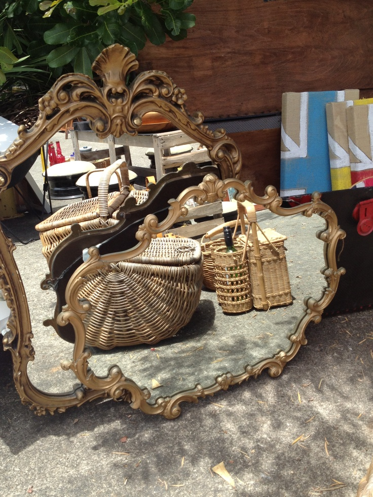 A pair of ornated gold gilded mirrors reflecting the day at Madam Sparrow's Market.