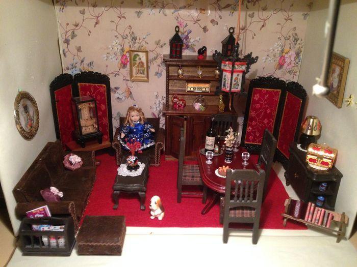 Zeer aparte eet- zit kamer met veel Chinese details. Hoge kast met 3 deuren en 3 planken , hoog 18 cm en breed 12 cm . Gevuld met 3 parfumflesjes en 3 beelden , i radio , 2 sierlampjes en vaas. 2 kamerschermen bekleed met Chinese rode zijde . 1 bank 2 zits 12 cm lang en 6 cm breed , bekleed met bruine suede [ heeft vlekjes ]  1 stoel met zelfde bekleding ,7 cm breed en 6 cm hoog. 1 bijpassende poef van 4 bij 5 cm . 1 kranten bak met krant en boekje . 1 eet tafel 6 cm hoog en 12 cm lang…