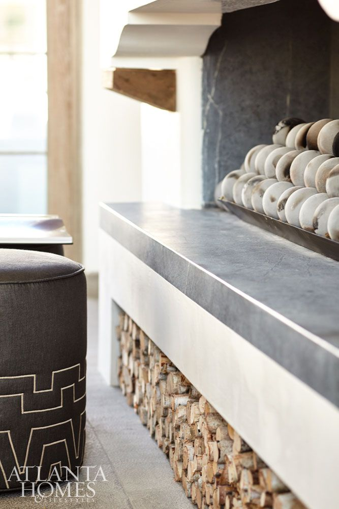 The soapstone hearth boasts circular clay balls while stacked birch logs add a decorative touch below the contemporary gas fireplace.