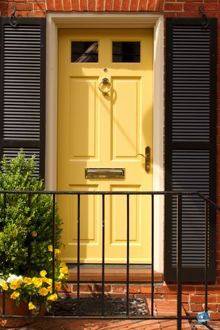 good colors for doors on brick houses | this front door scene with the vibrant yellow door surrounded