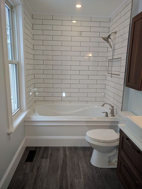 Simple bathroom for attic. Dark floors. White subway tile soft neutral walls. White vanity with brass or copper fixtures.
