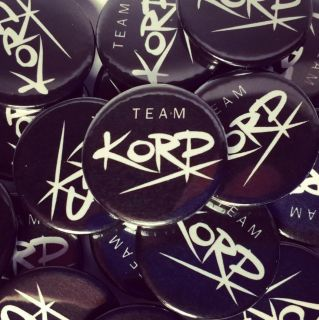 Four 25mm (1 inch) Korp button badges.