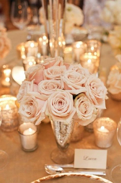 A feminine look is created with light pink roses in a mercury glass floral vessel surrounded by votives.