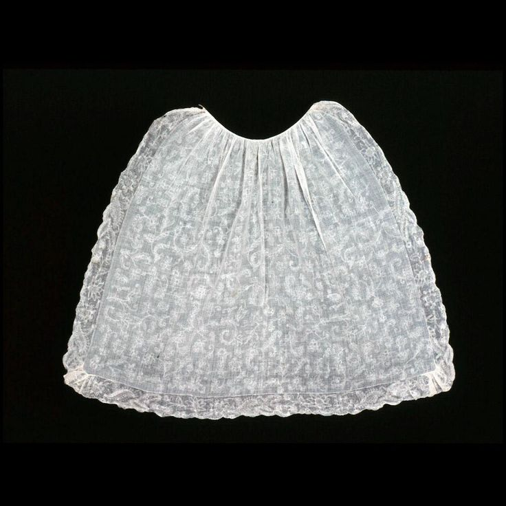 """Apron, whitework with ruffle ca. 1780 Origin: England OL: 31 (Center front) to 35 1/2"""" at sides; skirt width 46 1/2"""", gathered into 15"""" waistband. Linen embroidery on cotton ground; linen waist tape; linen sewing thread (microscope 5/8/09). Gift of Mrs. Cora Ginsburg. Acc. No. 1991-523"""