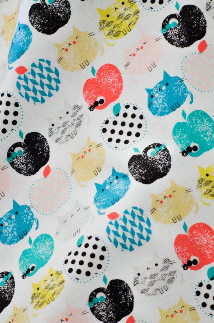 Divertida tela con dibujos de gatos y manzanas. En colores coral, verde y negro. Es de Dashwood Studio diseñada en el Reino Unido.