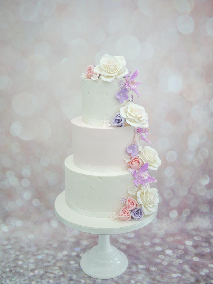 Bruidstaart met witte rozen en roze en paarse orchideeen en duimrozen.