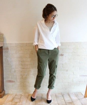 Summer casual style with a relaxed white button down shirt, olive ankle pants, and black ballet flats.