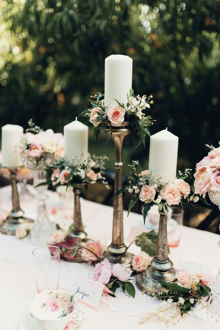 Vintage metallic silver candle holders with pretty pink roses and foliage.
