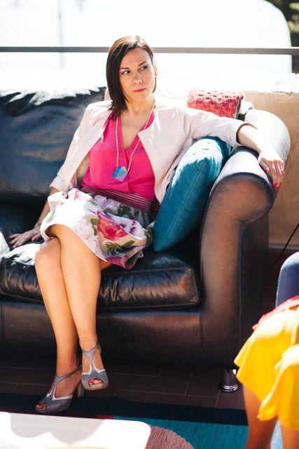 Elisa seduta sul divano nero in pelle dal forte carattere ma comodo e avvolgente. Il blu ed il rosa addolciscono l'insieme per un armonico arredo. www.lesorellemartini.it