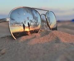 Wait till the sunset is going down and plant a pair of sunglasses in the sand!