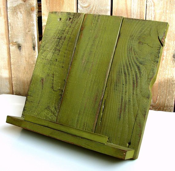 An olive green vintage style wooden Ipad/cookbook stand perfect for your kitchen or office and will create a warm, rustic vibe while adding functionality.  Tablet stands are 10 tall x 9 3/4 wide and are made of 3/4 thick recycled wood. Original piece by Alison