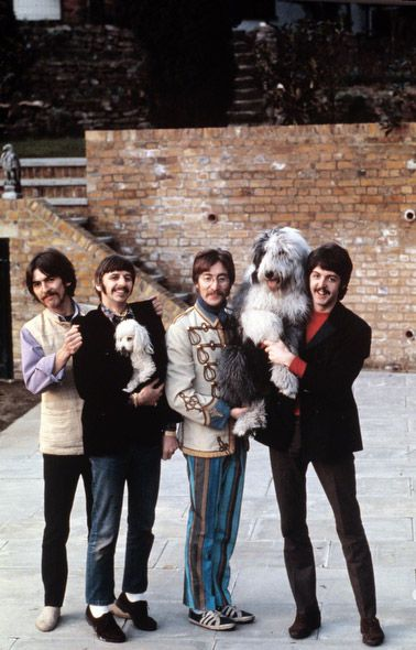 "The Beatles pose in Ringo Starr's backyard, 1967. McCartney holds his sheepdog Martha, who would later be the inspiration for the song ""Martha My Dear."" (Henry Grossman)"