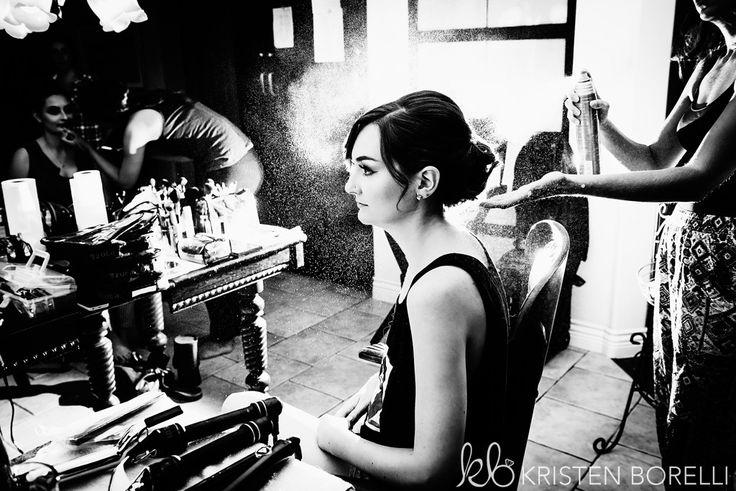 Bride getting hair done by hair stylist. Hairspraying brides hair.