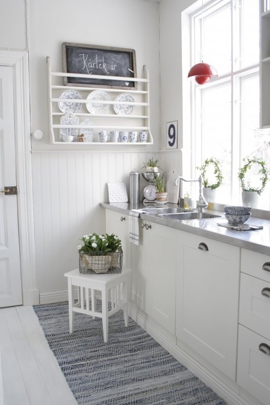 White kitchen with stainless counter top, perhaps with a couple of wooden (built in chopping board) and chicken themed things