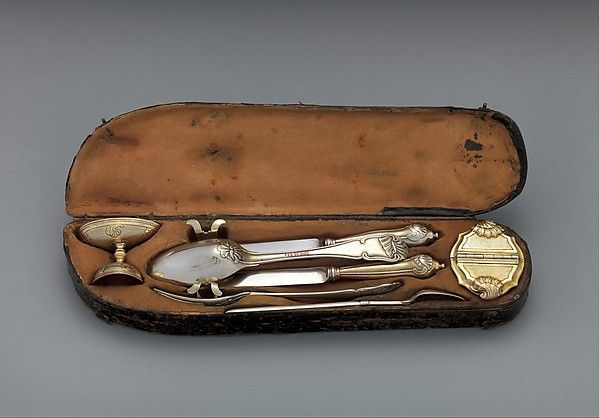 This compact set is similar to another in the museum's collection, acc. no. 2010.110.79a–i. However, here the case-maker, a separate craftsman from the goldsmith, has positioned the egg cup and spice box so that they frame and intensify the crowded impression of the utensils stored in between