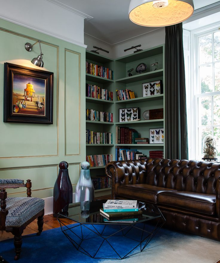 Panelled walls, built in bookcases with chesterfield sofa create a calming library space within this Georgain period home in Dublin. By Kingston Lafferty Design.
