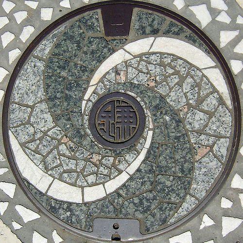 Japanese manhole cover | Au Japon les plaques qui recouvrent les bouches d'égouts sont souvent décorées et peintes avec des motifs représentant une spécialité de la ville où elles sont installées ou rendent hommage aux personnels qui les utilisent | In Japan, these covers are sometimes decorated with images specific to the city or the people who use them