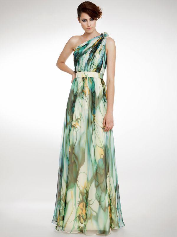 Precioso vestido estampado en tonos verdes, con escote asimétrico, cuerpo de tablas en diagonal, ceñido hasta la cintura por un cinturón de tonos más claros.