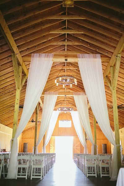 Indoor barn wedding ceremony decor idea - white fabric draped from the ceiling {Brandy Angel Photography}