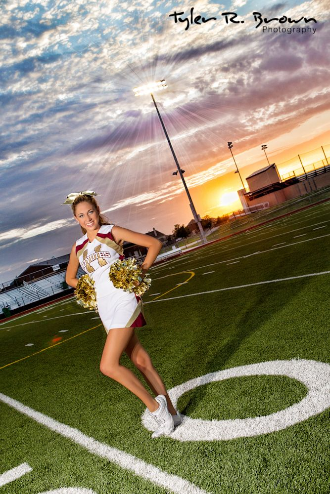 Heritage high school cheerleader, Skyler, poses with her pom poms, in front of a pretty sunset in Frisco.