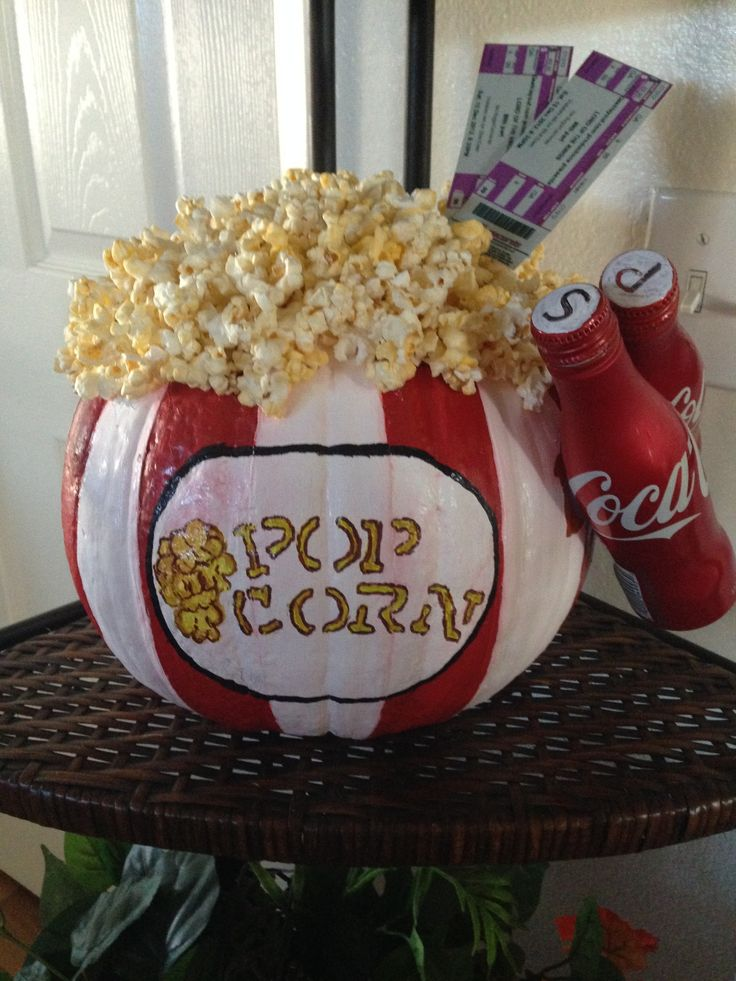 Made from an uncarved pumpkin. I used acrylic paints, printed out fake movie tickets, added two miniture coke cans and hot glued on popcorn. I used tape to help me achieve straight lines