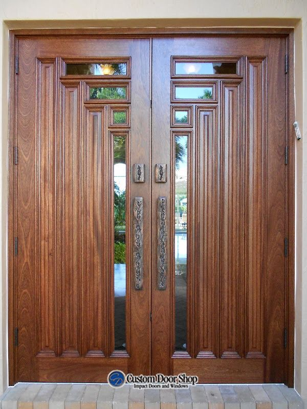 Unique wood front door. Modern art deco style double wood doors. Mahogany wood and impact glass paired with bronze pulls.