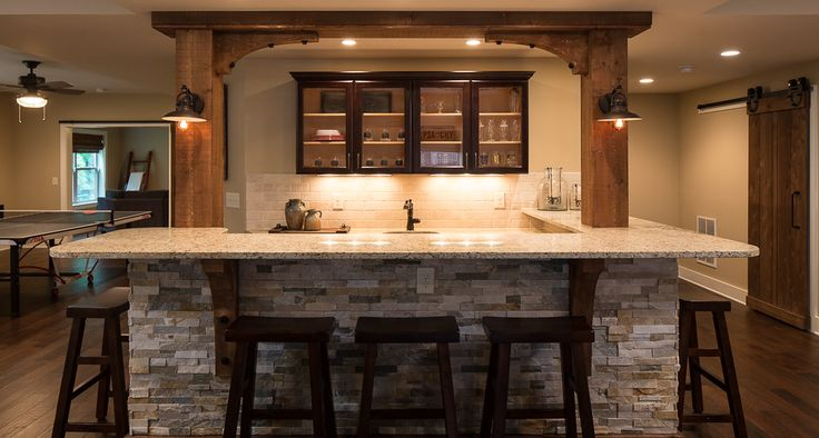 The U-shaped bar has split-face stone on all sides along with cedar beams and corbels for a rustic and yet industrial theme! The cabinets are stained dark with glass panels and undercabinet lighting.