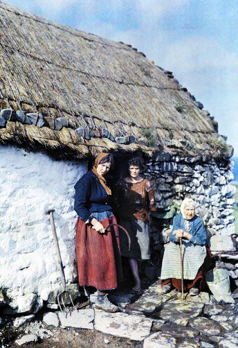 Three generations of peasant women stand outside their stone cottage, Connemara. 1920's. Clifton R. Adams (Photography)