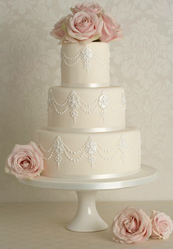 Baroque Pearl...Inspired by a baroque pearl necklace this beautiful cake is decorated with swags of hand piped pearls & floral cameos. Crowned with a cluster of fresh blush pink roses. As shown, serves 90
