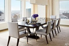 Modern dining table for 8 people in a Milwaukee Residence project by Victoria Hagan. Dark wood of the long dining table pairs beautifully with bright grey, upholstered dining chairs