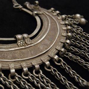 Gros collier Indien originaire du sud de l'Inde en alliage de métal blanc. Il est composé de deux chaines avec contrefort dans le cou et d'un pendentif massif en croissant de lune orné de grelots.