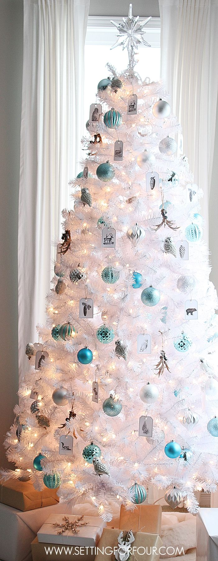 See how I decorated my Winter Woodland Glam White Christmas Tree for the holidays! DIY woodland animal ornament tags, blue and silver ornaments, antlers and simple white and brown craft paper gift wrap! www.settingforfour.com