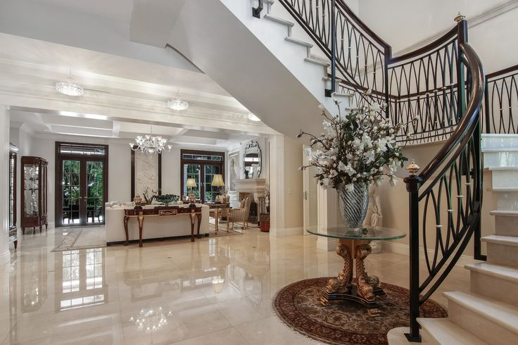 A stunning marble staircase with Italian custom iron railing, elegant crystal chandeliers, and other custom finished welcome you into this luxurious retreat.  #SupremeAuction #LuxuryAuction #Miami #CoralGables #MiamiMansion #MiamiRealEstate #Florida #FloridaRealEstate #ResortStyle #Auction #KoiPond #MediterraneanMansion