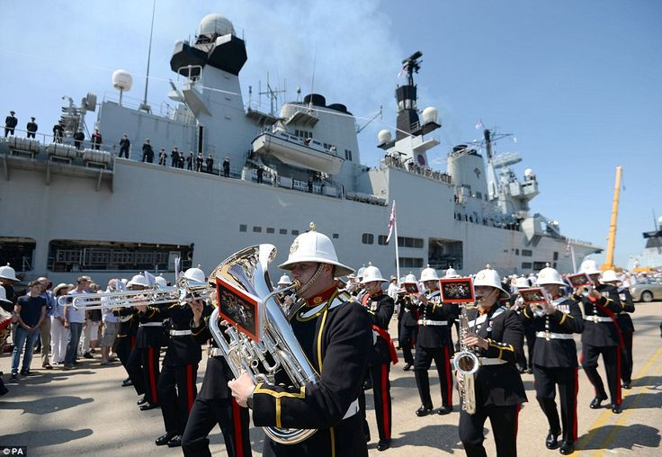 Music: The band of The Royal Marines perform next to HMS Illustrious as she sails into her home port of Portsmouth for the final time