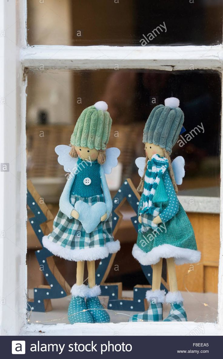 Download this stock image: Two christmas angel dolls in a shop window. Cotswolds, England - F8EEA5 from Alamy's library of millions of high resolution stock photos, illustrations and vectors.