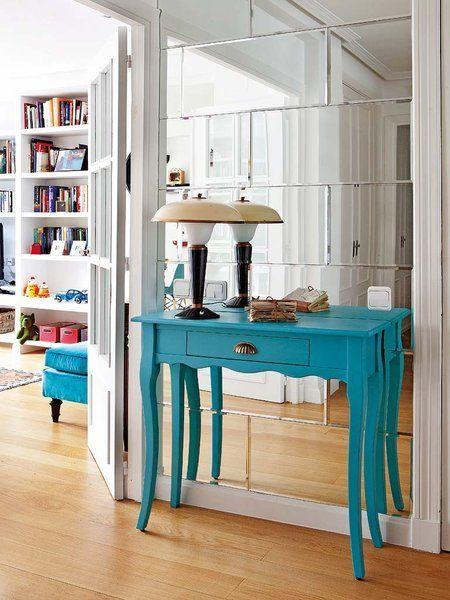 Un recibidor de espejos biselados con consola azul