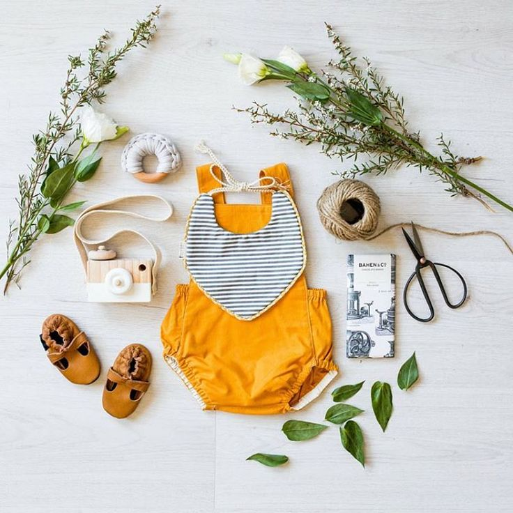 Our baby hamper box 'Little River' in a flatlay.    Box featuring romper soft soled shoes, wooden camera, chocolate, bib and a teether. #propstyling