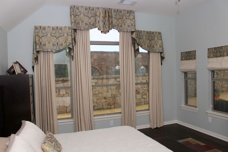 This difficult set of windows in a Master Bedroom provided a challenge with the three different heights!  We unified the main focal window, which you see as soon as you enter the bedroom, with one beautiful window covering!  The side windows are tastefully treated with roman shades in the same fabrics as the large window but do not take attention away from this beautiful focal point in the room.