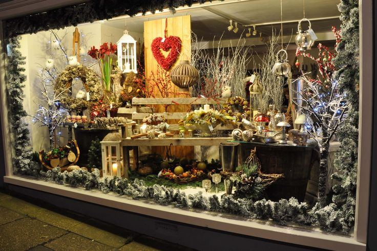 A Christmas window display of a florists. This florist have used an outdoor setting as their inspiration. It used both modern and traditional influences.