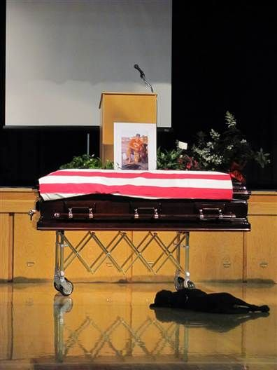 Labrador Hawkeye lies down beside his owner, Navy SEAL Jon Tumlinson's coffin